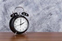 de klok uitstekende klok van 2 o ` op houten lijst en muurachtergrond Royalty-vrije Stock Afbeeldingen