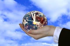 De klok van de de holdingsbol van de hand Stock Afbeeldingen
