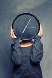 De klok van de jong kindholding voor hoofd Stock Fotografie