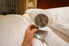 De klok van de vrouwengreep voor alarm die in slaapkamer plaatsen Royalty-vrije Stock Foto