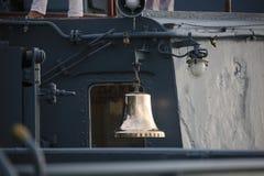 De klok van het messingsschip met de naam van het schip op de achtergrond van de bovenbouw stock afbeelding