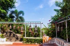 De klokken van Boedha hangen op een rij omringd door groene bomen en bloemen stock foto