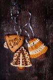 De klokkenkoekjes van de Kerstmis eigengemaakte peperkoek op donkere houten tabl stock afbeeldingen