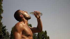 De knappe aantrekkelijke atleet giet water in zijn mond en over zijn hoofd stock video