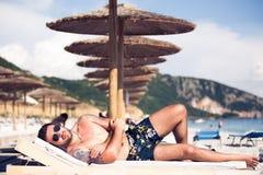 De knappe aantrekkelijke spier sunbed en mens die liggen ontspannen Knappe mens met tatoegering het zonnebaden, spf bescherming e Stock Afbeelding