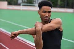 De knappe Afrikaanse atletenmens maakt uitrekkende oefeningen Royalty-vrije Stock Foto's