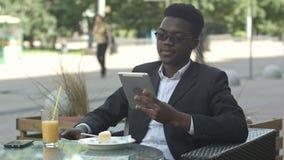 De knappe afro Amerikaanse mens gebruikt een tablet, terwijl het zitten in buitenkoffie stock footage