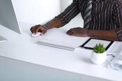 De knappe Amerikaanse zakenman van Afro in klassiek kostuum gebruikt laptop en glimlacht terwijl het werken in bureau Royalty-vrije Stock Afbeeldingen