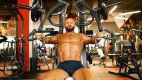 De knappe atleet oefent in gymnastiekcentrum uit Bodybuildermens harde opleidingsspieren bij opleidingsmachine stock video