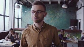De knappe bedrijfsmens komt aan modern bureau op het werk Het jonge mannetje begroet met collega's, brengt koffie aan vrienden la stock video
