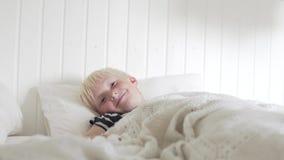 De knappe blonde jongen ligt in de ochtend op het bed stock footage