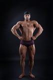 De knappe bodybuilder toont zijn krachtig lichaam aan Stock Afbeelding