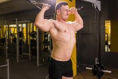 De knappe bodybuilder werkt oefening in gymnastiek uit Royalty-vrije Stock Afbeelding