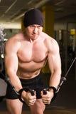 De knappe bodybuilder werkt oefening in gymnastiek uit Stock Fotografie