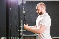 De knappe bodybuilder werkt oefening in gymnastiek uit Royalty-vrije Stock Foto