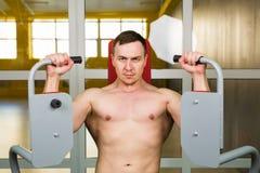 De knappe bodybuilder werkt oefening in gymnastiek uit Stock Foto