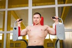 De knappe bodybuilder werkt oefening in gymnastiek uit Royalty-vrije Stock Foto's