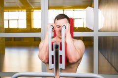 De knappe bodybuilder werkt oefening in gymnastiek uit Royalty-vrije Stock Fotografie