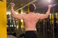 De knappe bodybuilder werkt oefening in gymnastiek uit Stock Foto's