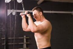 De knappe bodybuilder werkt oefening in gymnastiek uit Stock Afbeelding