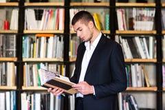 De knappe boeken van de jonge mensenholding en het glimlachen terwijl status in bibliotheek Stock Afbeelding