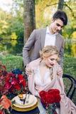 De knappe bruidegom die zijn bruid koesteren door shooulders bij de feestelijke lijst De herfsthuwelijk kunstwerk royalty-vrije stock foto's