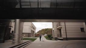 De knappe bruidegom en de charmante bruid brengen samen tijd na huwelijksceremonie in door het park stock video