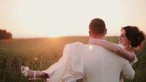 De knappe bruidegom houdt zijn mooie bruid in zijn wapens en wervelt rond Zij lacht en kust hem Zonsondergang in aard stock video