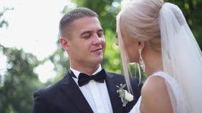 De knappe bruidegom koestert zijn mooie bruid Jonggehuwden die in het park lopen Blonde haarvrouw in elegante huwelijkskleding stock video