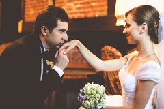 De knappe bruidegom kust de gevoelige hand van de bruid Royalty-vrije Stock Foto's