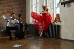 De knappe cellist bezoekt de muse van fairytale in rode kleding royalty-vrije stock afbeelding