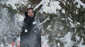 De knappe dame schudt de sneeuwsparrentakken in het park stock video