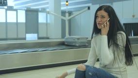 De knappe dame wacht op haar bagage bij de luchthaven en spreekt op de telefoon stock videobeelden