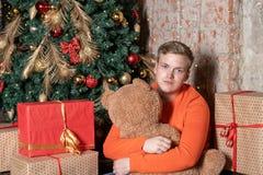 De knappe die kerel koestert de beerzitting onder de boom door dozen van giften wordt omringd Kerstmis en giften stock foto