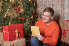 De knappe die kerel schrijft een brief aan Kerstman zittend onder de boom door vakjes van giften wordt omringd Kerstmis en giften stock fotografie