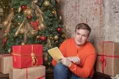 De knappe die kerel schrijft een brief aan Kerstman zittend onder de boom door vakjes van giften wordt omringd Kerstmis en giften royalty-vrije stock foto