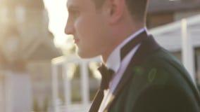 De knappe donkerbruine bruidegom in zwarte huwelijkskostuum en vlinderdas komt tot mooie bruid en geeft haar een kus Huwelijk stock footage