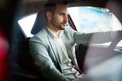 De knappe elegante ernstige mens drijft een auto stock fotografie
