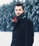 De knappe elegante gebaarde mens die van het manierportret zwarte laag in de winter over sneeuwbomen bosachtergrond dragen Royalty-vrije Stock Fotografie