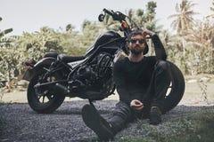 De knappe fietsermens in zwarte slijtage zit dichtbij klassieke de raceautomotorfiets van de stijlkoffie naar maat gemaakte motor royalty-vrije stock fotografie