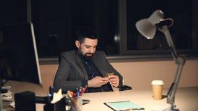 De knappe gebaarde jonge mens gebruikt smartphone wat betreft het scherm en glimlacht het werken in bureau laat bij alleen nacht stock videobeelden
