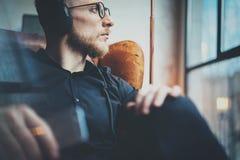 De knappe gebaarde mens die van het close-upportret in hoofdtelefoons aan muziek via mobiele telefoon bij moderne zolder luistere stock fotografie