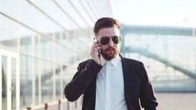 De knappe gebaarde mens die in zonnebril dichtbij de luchthaventerminal lopen, beantwoordt het telefoongesprek, knopen Modieuze e stock footage