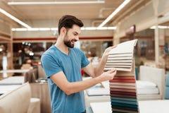 De knappe gebaarde mens kiest kleur op kleurenpalet Het selecteren van kleur van matras op de gids van het kleurenpalet Stock Foto's
