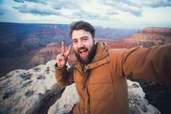 De knappe gebaarde mens maakt selfie foto op reis wandelend in Grand Canyon in Arizona Stock Foto
