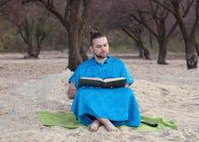 De knappe gebaarde mens met broodje op hoofd in blauwe kimonozitting verzendt, holding geopend boek royalty-vrije stock foto