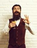 De knappe gebaarde mens met lange baard en snor heeft modieus haar bij het glimlachen van het glas van de gezichtsholding van alc stock afbeelding