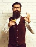 De knappe gebaarde mens met lange baard en snor heeft modieus haar op het ernstige glas van de gezichtsholding van alcoholische d royalty-vrije stock foto