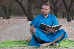 De knappe gebaarde mens met maakt omhoog, broodje op hoofd in blauwe kimonozitting, holding geopend groot boek stock afbeelding