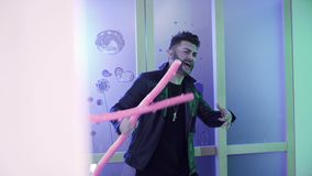De knappe gebaarde mens met modieuze haarbesnoeiing in jasje danst met roze kruis stock videobeelden